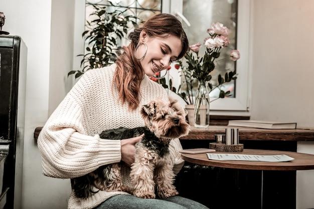 Ulubiony zwierzak. kobieta szczęśliwie trzymająca swojego małego psa