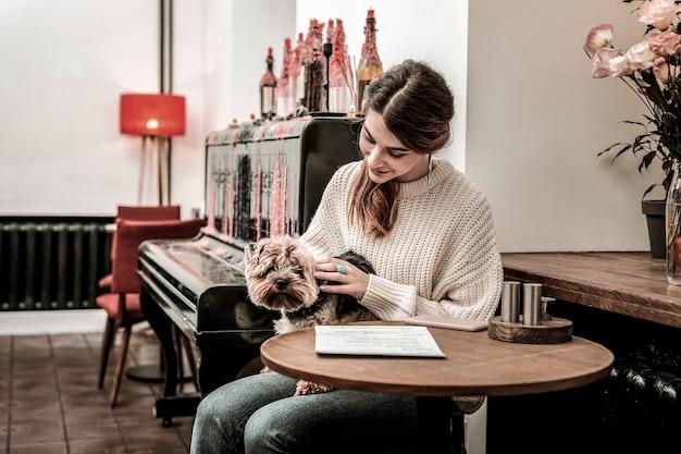 Ulubiony zwierzak. szczęśliwa kochanka głaszcząca swojego teriera siedząc w kawiarni