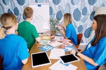 Umiejętna drużyna analizuje ogólnospołecznego medialnego wykres przy miejscem pracy