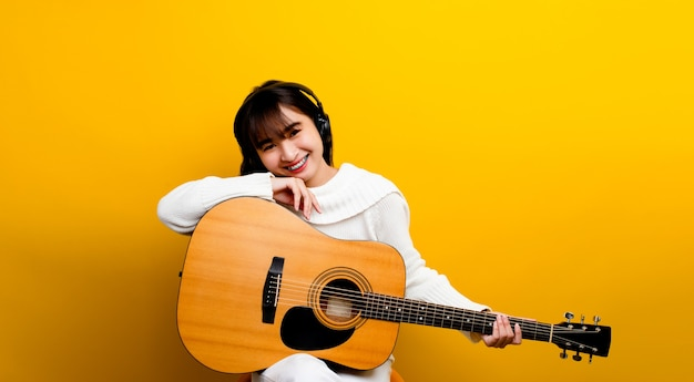 Umiejętność gry na gitarze asian girl piękna kobieta gra na gitarze klasycznej uśmiecha się i śmieje się głośno. i lubił grać jego muzykę.