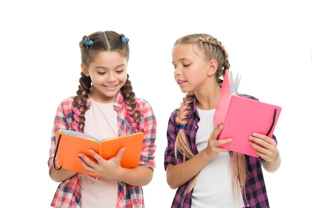 Umiejętności czytania. śliczne małe dzieci trzymające książki. urocze dziewczynki ze szkolnymi zeszytami. przygotowywanie zeszytów ćwiczeń do pisania. ucz się języka. zdobądź wiedzę. koncepcja edukacji.