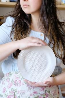 Umiejętności rzemiosła garncarskiego. tradycyjna sztuka tworzenia ceramiki. garncarz trzymający talerz gliny. koncepcja naczynia rzemieślnicze