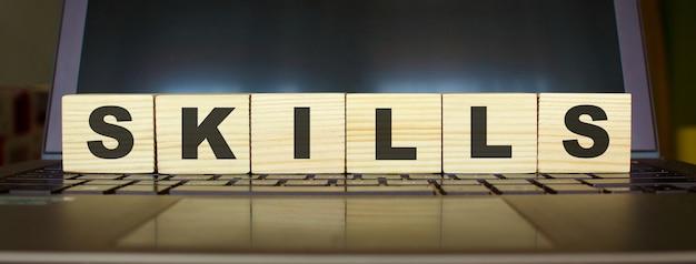 Umiejętności słowe. drewniane kostki z literami na białym tle na klawiaturze laptopa.