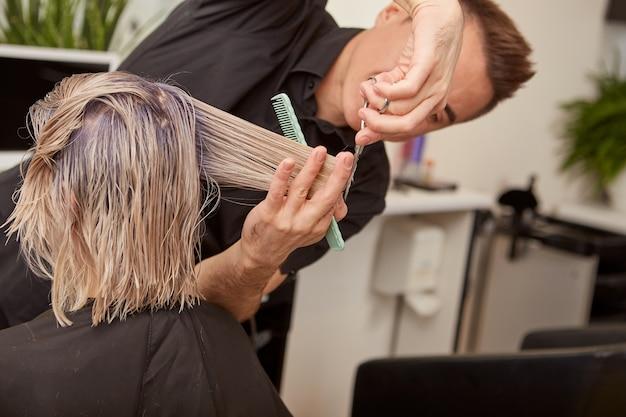 Umiejętny fryzjer strzyżenia kobiecie blond włosy w salonie kosmetycznym