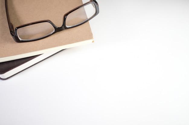 Umieść notatnik i okulary na białym stole.