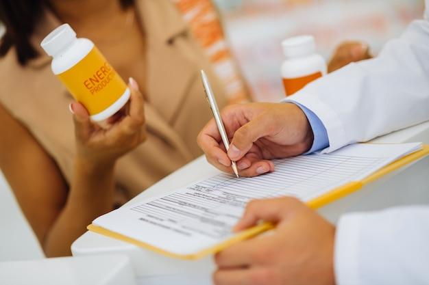 Umieść swój znak. skupione zdjęcie na męskiej dłoni, które robi notatki podczas konsultacji