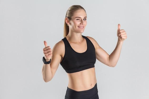 Umięśniona dziewczyna pokazująca kciuki do góry przed kamerą i mrugająca