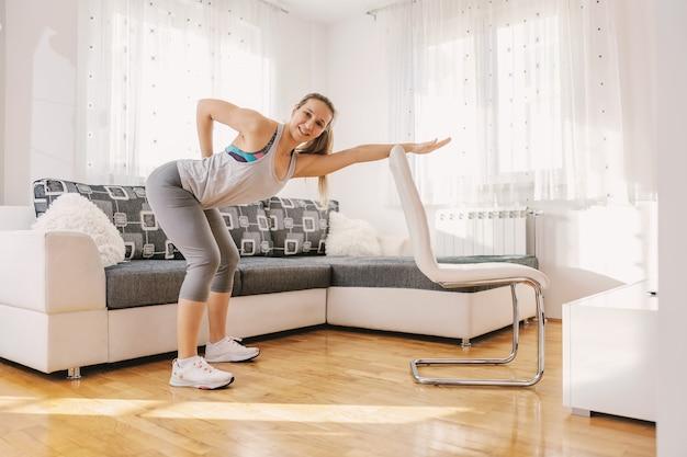 Umięśniona sportsmenka w formie ćwiczeń fitness na plecach, opierając się na krześle. jeśli nie możesz chodzić na siłownię, możesz zrobić własną w domu.
