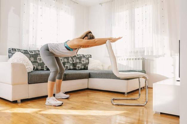 Umięśniona sportsmenka w formie ćwiczeń fitness na plecach, opierając się na krześle.