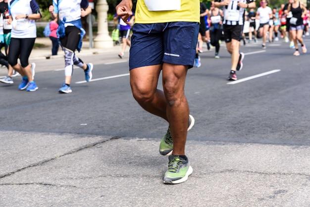 Umięśnione nogi czarnego biegacza startującego w amatorskim wyścigu ulicami walencji w hiszpanii.