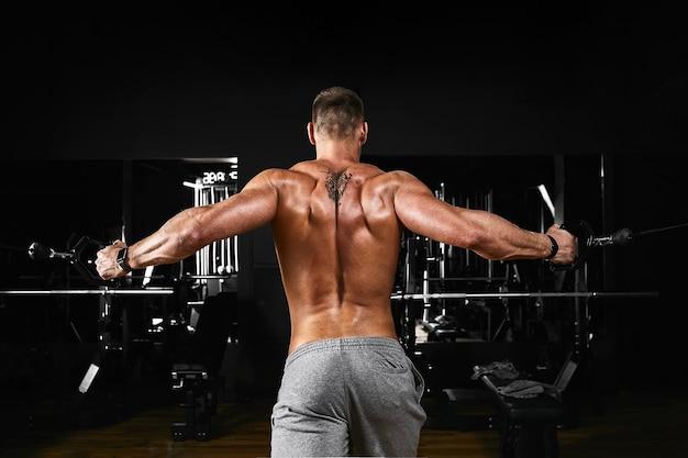 Umięśniony mężczyzna bez koszuli ćwiczy biceps z hantlami