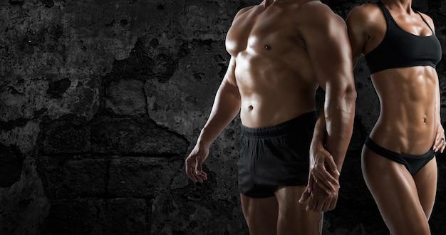 Umięśniony mężczyzna i kobieta trenują na siłowni