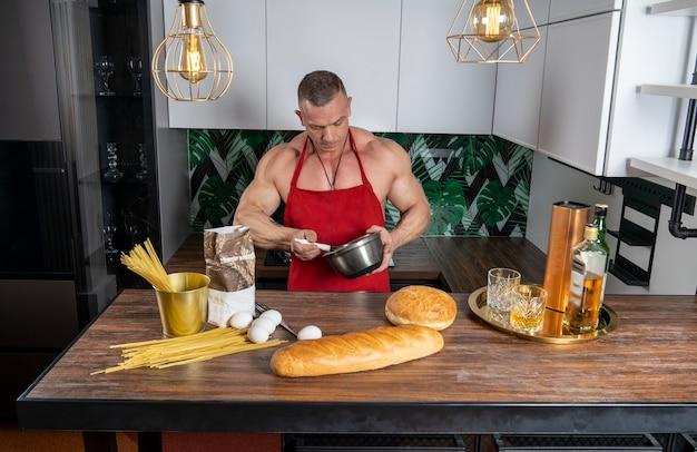 Umięśniony mężczyzna w kuchni przygotowuje danie obok produktów na stole to whisky