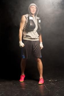 Umięśniony młody bokser przygotowuje się do walki