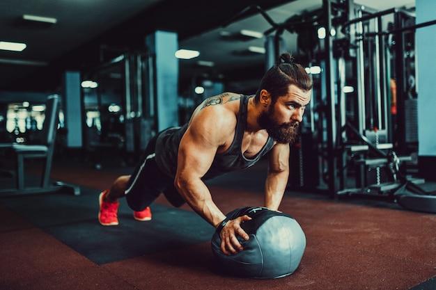 Umięśniony młody człowiek jest ubranym sport odzież i robi deski pozyci podczas gdy ćwiczący na podłoga w loft wnętrzu
