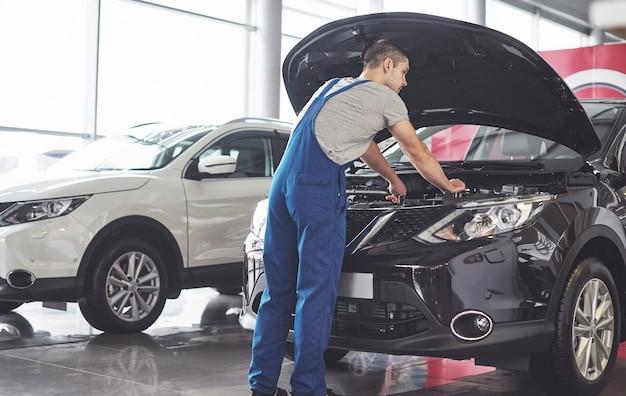 Umięśniony pracownik serwisu samochodowego naprawy pojazdu.
