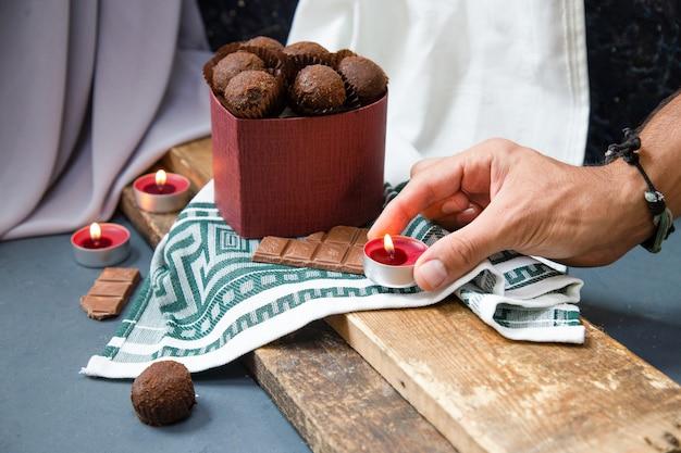 Umieszczenie płonących świec wokół czekoladowego pudełka na kawałku drewna