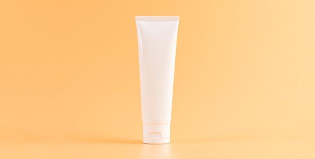 Umieszczona butelka leku, pusty pakiet etykiet na pomarańczowej ścianie. pojęcie naturalnych kosmetyków.