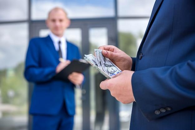 Umowa biznesowa na zewnątrz, partnerzy z banknotami dolarowymi
