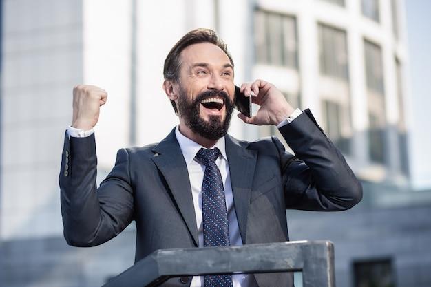 Umowa biznesowa. zadowolony z profesjonalnego biznesmena, który dzieli się swoimi emocjami podczas świętowania zwycięstwa przez telefon