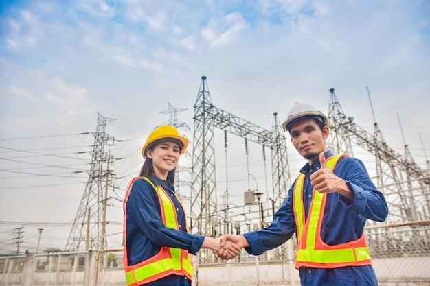 Umowa dwóch inżynierów podających sobie ręce w systemie fabryki elektrowni
