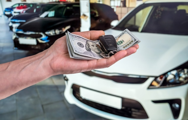 Umowa kupna kupna lub wynajmu nowego samochodu. ręka z dolarowymi pieniędzmi i kluczykami do samochodu. finanse