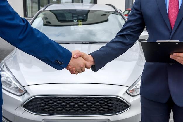Umowa kupna samochodu między dwoma mężczyznami na zewnątrz
