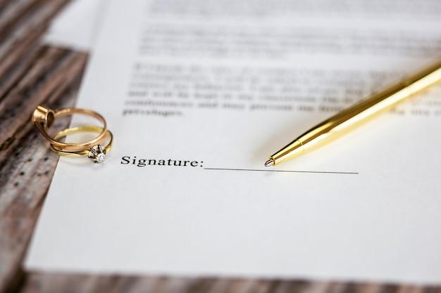 Umowa małżeńska z dwoma złotymi obrączkami i złotym długopisem, umowa przedmałżeńska, makro z bliska, podpisanie z podpisem, dokument, romans koncepcja umowy