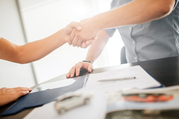 Umowa między dwoma młodymi mężczyznami. podają sobie ręce. na stole leży długopis, dziennik i inne dokumenty. światło dzienne z okna