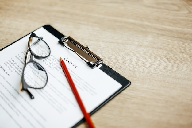 Umowa na drewnianym stole roboczym z okularami i czerwonym ołówkiem. dokumenty są gotowe do podpisania. pomysł na biznes. umowa o współpracy.
