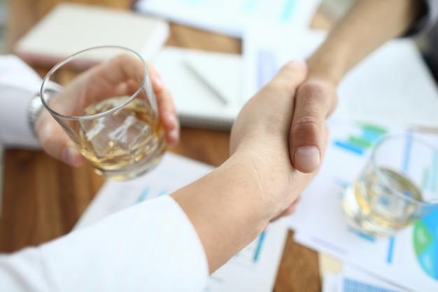 Umowa o zawarciu uścisku dłoni przy stole roboczym.