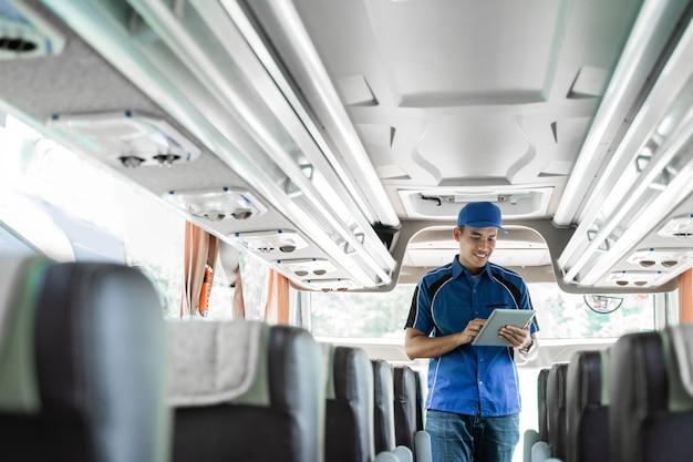 Umundurowany członek załogi autobusu korzysta z cyfrowego tabletu podczas sprawdzania biletów online, stojąc w autobusie