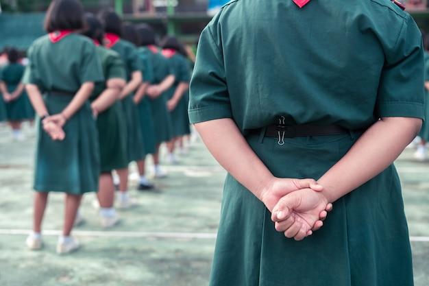 Umundurowany harcerz stoi z rękami za plecami w szkole