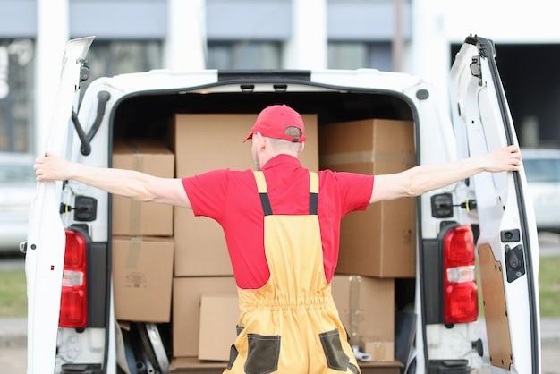 Umundurowany kurier otwiera bagażnik minivana wypełniony kartonami