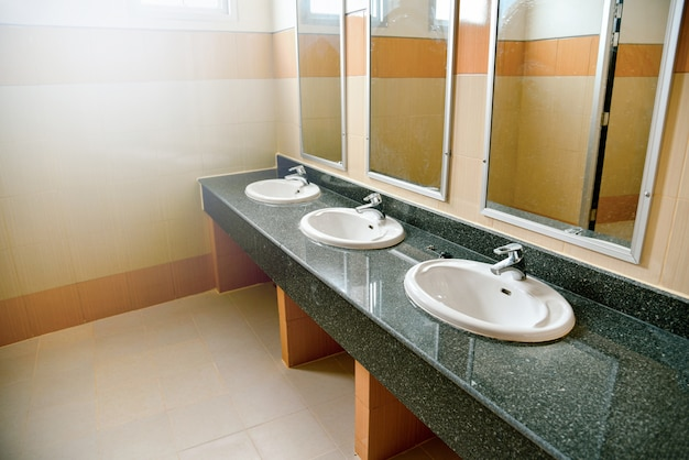 Umyj umywalkę i lustra w białej łazience w publicznej toalecie