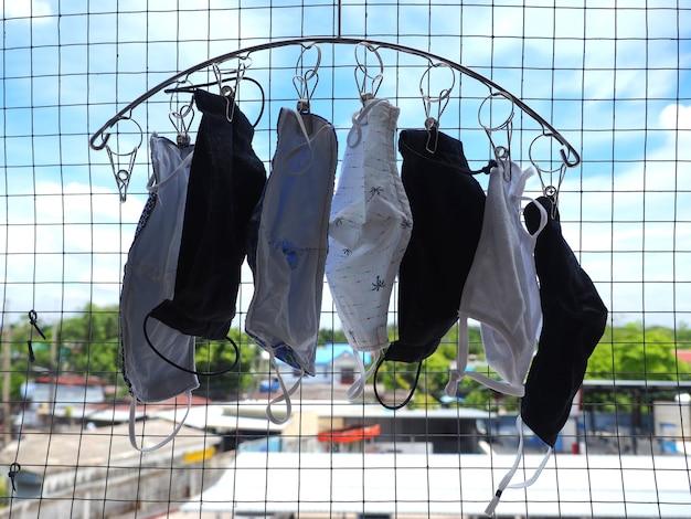 Umyta i wysuszona maska z ręcznie robionej tkaniny wisząca na wieszaku na ubrania w zacienionym tarasie mieszkania. maska z tkaniny służy do zakrycia twarzy. zapobiegaj zakażeniu epidemią covid-19. wisząca tkanina