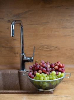 Umyte owoce czerwone i zielone winogrona leżą w pobliżu zlewu w kuchni
