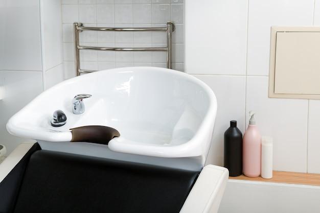 Umywalka do mycia włosów we wnętrzu salonu kosmetycznego lub fryzjera, szampony, kosmetyki do włosów do zabiegów spa. miejsce pracy fryzjera stylisty. miska fryzjerska, sprzęt do mycia.