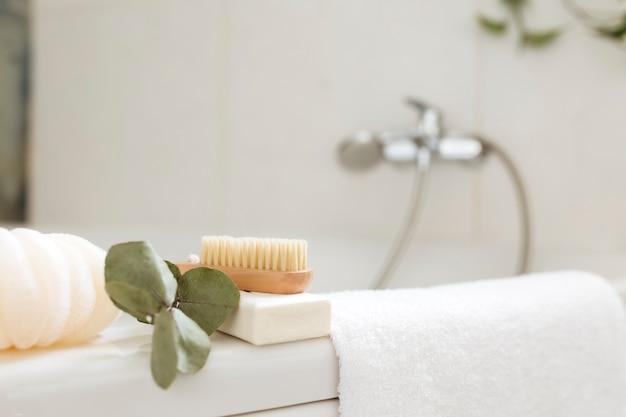 Umywalka w białej łazience z akcesoriami do kąpieli. koncepcja czyszczenia hotelu. koncepcja gospodarstwa domowego. myjka, mydło, szczotka do stóp, ręcznik i gałązka eukaliptusa z zielonymi liśćmi.