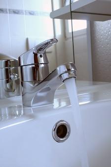 Umywalka w łazience z wodą spływającą z kranu