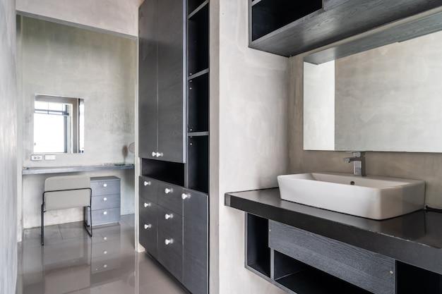 Umywalka w nowoczesnej łazience w stylu loftu z szafą w łazience