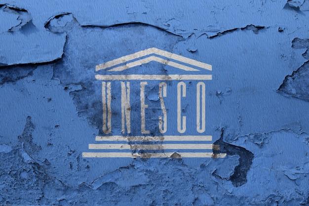 Unesco flaga malująca na grunge pękającej ścianie