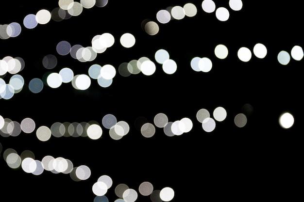 Unfocused abstrakcjonistyczny biały bokeh na czarnym tle. niewyraźne i zamazane wiele okrągłych świateł