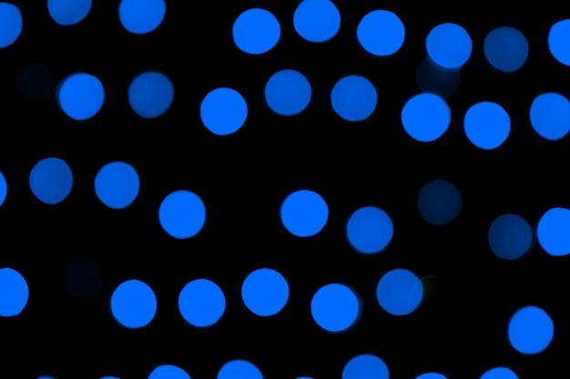 Unfocused abstrakcjonistyczny zmrok - błękitny bokeh na czarnym tle. niewyraźne i zamazane wiele okrągłych świateł
