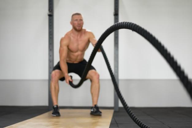 Unfocused nierozpoznawalny człowiek siłownia bitwa liny trening wytrzymałościowy facet sportowiec ćwiczenia wytrzymałościowe trening w pomieszczeniu. przystojny kaukaski facet sprawny robi ćwiczenia fitness trening funkcjonalny.