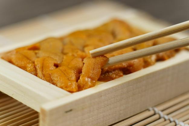 Uni sushi w pałeczkach. jeżowca (uni sashimi), japońskie jedzenie.