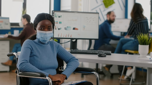 Unieruchomiony sparaliżowany niepełnosprawny afrykański pracownik patrzący na kamerę w masce ochronnej podczas ...
