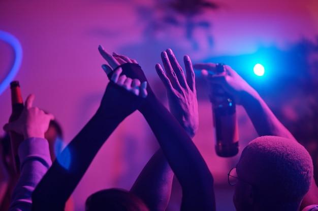 Uniesione ramiona młodych podekscytowanych międzykulturowych przyjaciół tańczących na domowej imprezie i pijących drinki przed różowymi światłami podczas weekendu