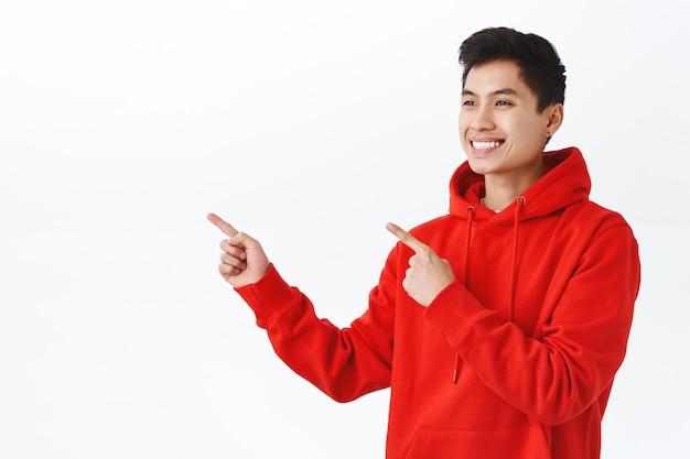 Uniesiony do pasa portret zadowolonego, szczęśliwego przystojnego azjatyckiego męskiego ucznia w czerwonej bluzie z kapturem, kolczyk, patrzący i wskazujący palce pozostawiony z zadowolonym wyrażeniem, poleca dobry produkt, biała ściana.