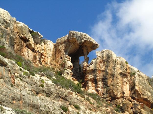 Unikalna naturalna formacja cienia skalnego na klifie doliny wied babu na malcie na błękitnym niebie